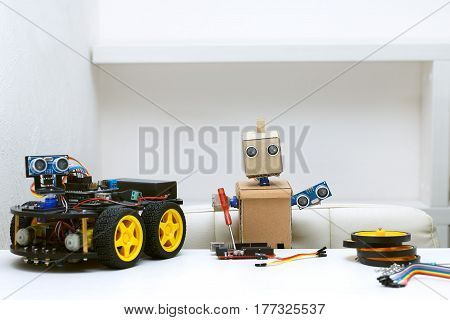 The robot holds in its hands the parts for assembling the robot and next to it is a robot with wheels