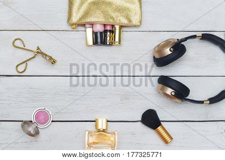 Female accessories cosmetics pink and gold colors on a wooden white background