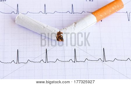 Cigarette and EKG printout. Cigarette and health of heart.