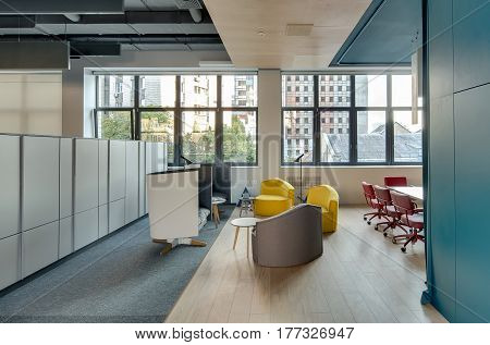 Coworking in a loft style with light walls and large windows. There is a relax zone with different soft armchairs and small round wooden tables, table with red chairs, lockers, hanging fancy lamps.