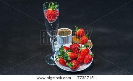 Black Coffee In White Cup, With Croissants On Saucer, Sparkling Wine, Strawberry