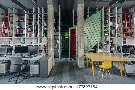Loft style office with concrete columns and a gray carpet. There is a metal green-red stairway tunnel-structure, yellow table with chairs, gray workplaces with computers, shelves with red ladders.