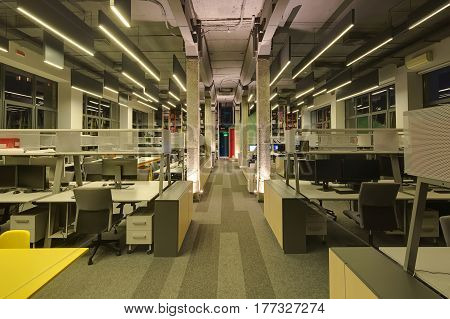 Office in a loft style with many glowing hanging lamps, gray walls, concrete columns and a carpet on the floor. There are many workplaces with computers and metal reticulated shelves and lockers.