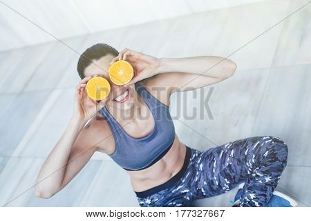 Fit and healthy personal trainer playing with oranges