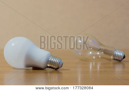 Two light bulbs. LED white and ordinary incandescent lamp on wooden background