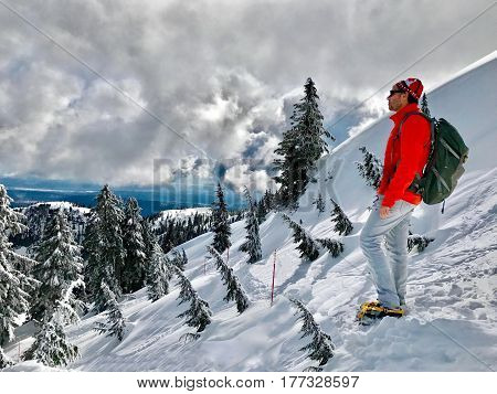 Man hiker in scenic winter mountains. Mount Seymour Park. Hiking trail to the first peak. North Shore. Vancouver. British Columbia, Canada.