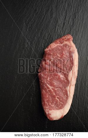 Raw steak of marbled Angus beef on a slate cutting board