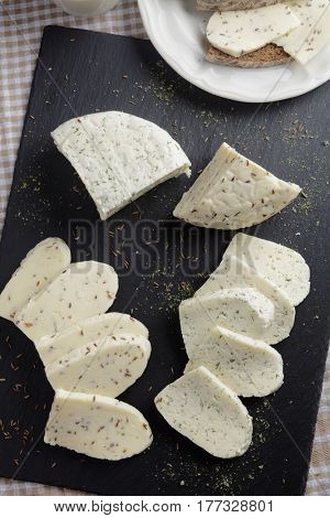 Estonian cheeses with cumin, dill, and garlic on a slate cutting board