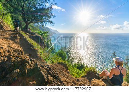 Young woman resting in amazing Kalalau trail, Kauai Island, Hawaii