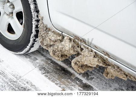 close up on tire of car with snow and ice