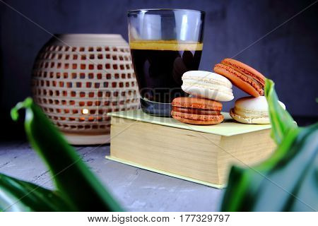 cookies macaroon with a Cup of coffee,a book and a candlestick