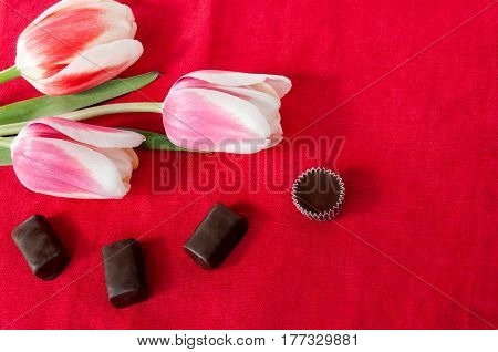 Tulips And Chocolate Candies On A Red Background