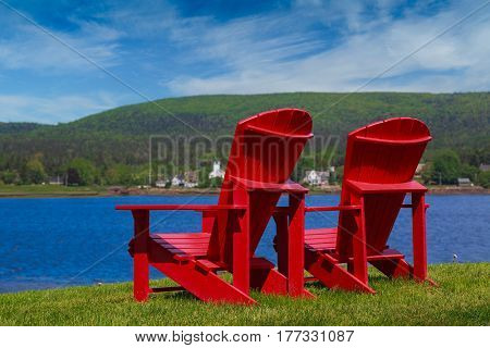 Two red Adirondack chairs overlooking the Annapolis River, Nova Scotia, Canada,