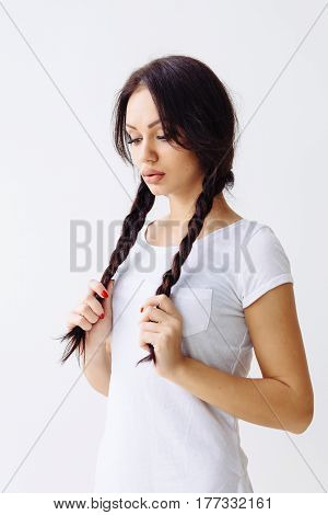 Young pretty woman serious looking at camera. Perfect skin and hairstyle with pigtails. White background not isolated