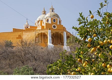 Section of Our Lady of Los Remedios church in Cholula Mexico with orange tree in foreground