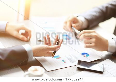 Image of two young businessmen discussing document  at meeting