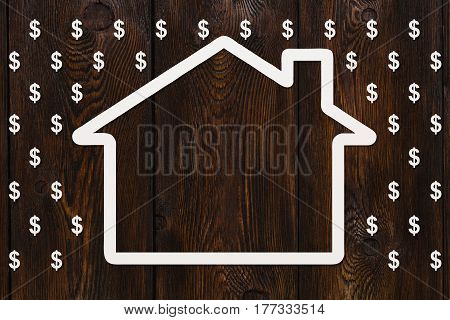 Paper house in rain of dollars on wooden background money concept. Abstract conceptual image