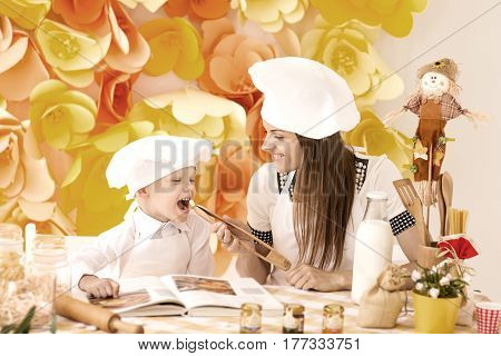 A happy mother and her child in the form of cooks prepare a delicious dinner in the kitchen
