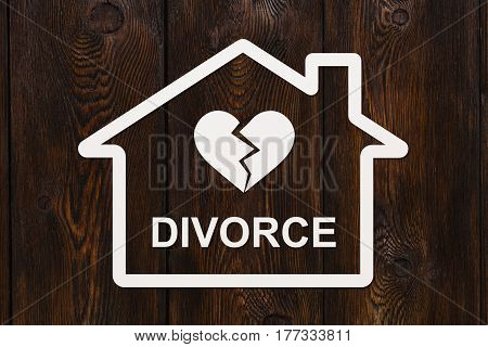 Paper house with broken heart and text DIVORCE inside. Abstract conceptual image