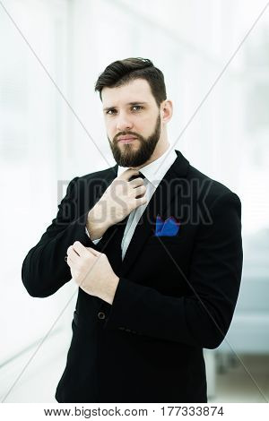 portrait of a successful businessman adjusting his necktie while standing near a window in bright office.the photo has a empty space for your text