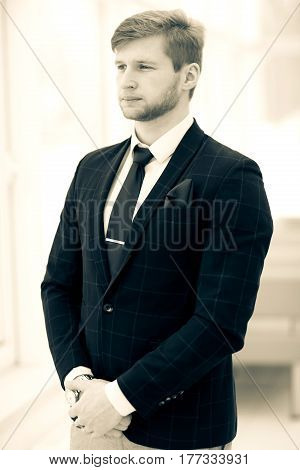 photo in retro style - beginner businessman in a business suit stands near the window, hands folded in front of him .the photo has a empty space for your text