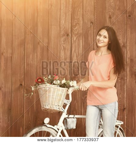 A romantic young woman looking at the camera with her bike and a basket of wildflowers. Summer.