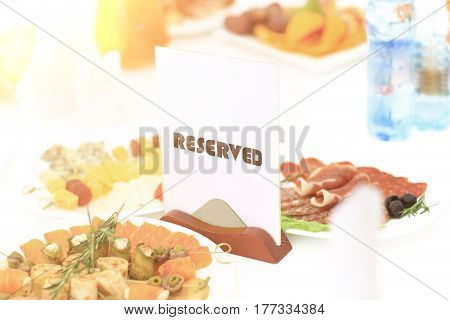 A reserved sign the restaurant table in bright sunny weather against a background of dishes