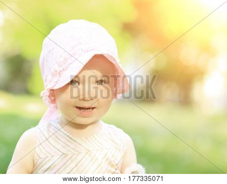 Portrait of a little girl in a panama in the park on a sunny day