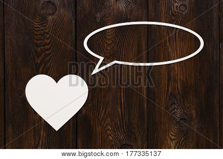 Paper heart is talking or thinking on wooden background. Abstract conceptual image with copyspace