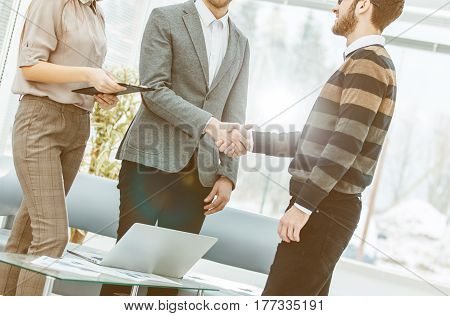 handshake of a Manager and a customer on the background of the office.the photo has a empty space for your text.