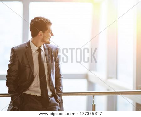 Portrait of a smiling handsome businessman on window background looking to the side of a virtual text