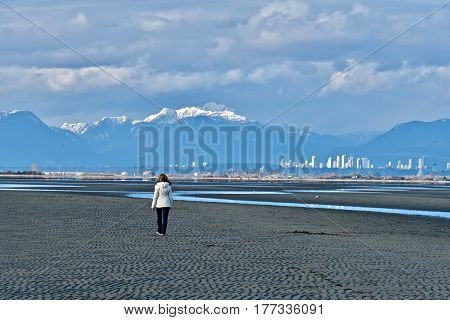 Woman walking on beach with downtown Vancouver and mountains view. Boundary Bay Regional Park in Tsawwassen. Great Vancouver. British Columbia. Canada.