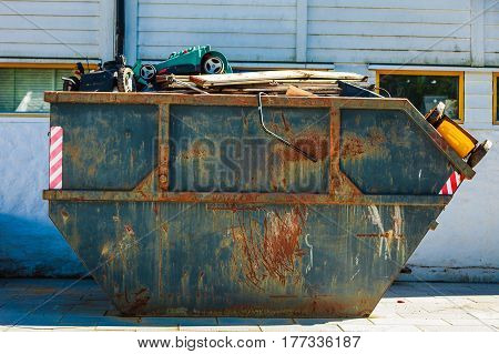 Outdoor shot of heavy dark industrial trash waste dumpster container in factory.