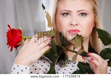Romance valentine day gifts concept. Beautiful blonde young woman holding red rose near face looking melancholic