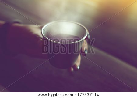 black coffee is served hot in stainless steel cup on wood table in cafe.