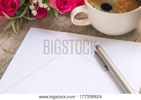 white blank note and pen on table with cup of coffee background