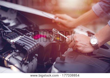 cropped image of man hand repairing a broken car sunlight effect