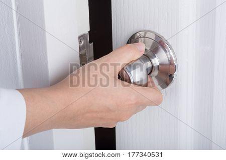 Hand Opening Door Knob On White Door