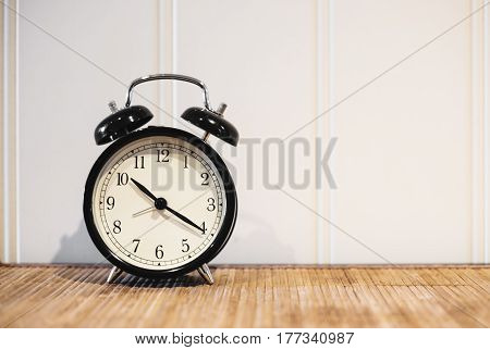 Retro alarm clock with 10 O'clock and twenty minuet, on wooden table and white background with copy space