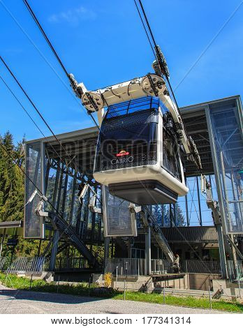 Mt. Stanserhorn, Switzerland - 8 May, 2016: a gondola of the Cabrio cable car starting its way to the top of the mountain from the Kalti station. Stanserhorn Cabrio is the the world's first double deck open top cable car.