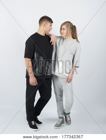 Girl leans on boy's shoulder. Young muscular man wearing black clothes and sneakers with girl in grey clothes solated on white background