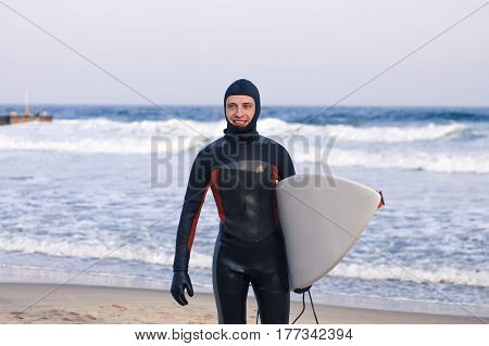 Surfer goes out of water wearing a wetsuit. He is holding white sufrboard