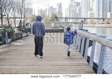March 27 2017- Father and Son walking at the seawall in Granville island Vancouver,BC Canada