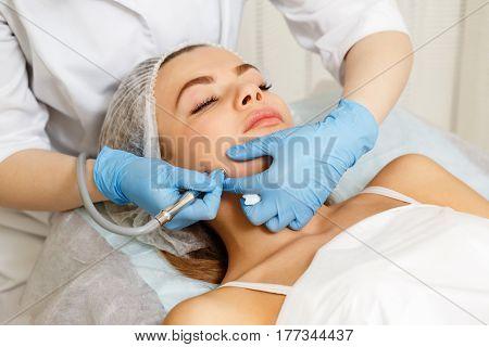 Dermabrasion cheekbones girl. Instrumental cosmetology. Spa. Facial Rejuvenation. Mechanical peeling skin. poster
