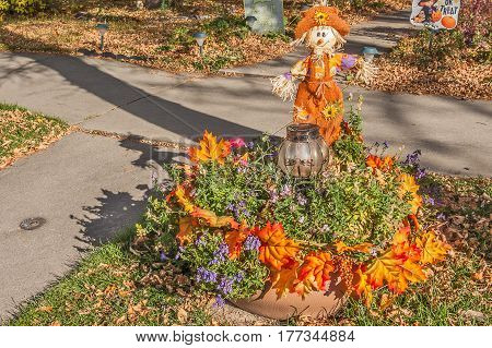Scarecrow dressed in orange welcomes visitors to his home