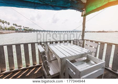 White dining table on corner of indoor beach terrace over water surface. Terrace surrounded by wooden wall and covered by colorful canvas.