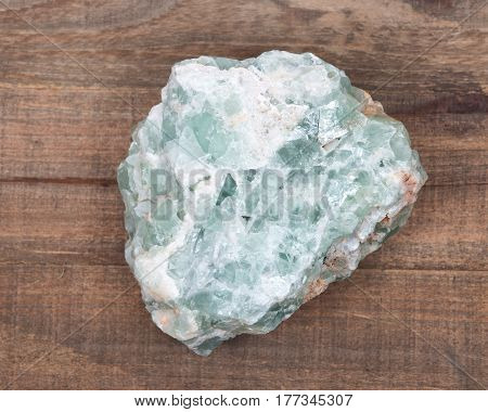 Raw green fluorite natural chunk on wooden vintage tray background