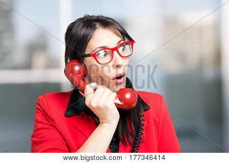 Red dressed business woman using a vintage telephone