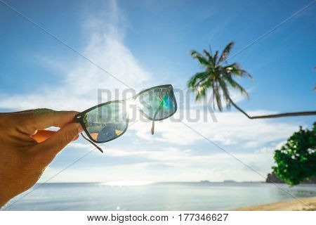 Sunglasses in hand against a background of tropical landscape of palm trees and beach. Sunlight through sunglasses. Conceptual background of a beach holiday.