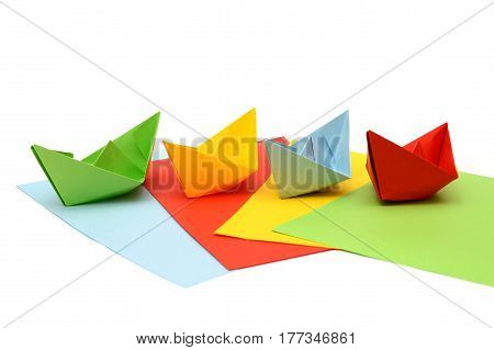Ships origami. Paper boats on colored sheets. Colorful figures. Transport origami